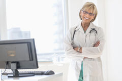 Lycklig mogen kvinnlig doktor Standing Arms Crossed i sjukhus Royaltyfri Foto