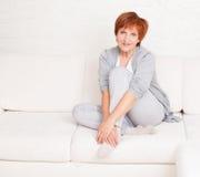 Lycklig mogen kvinnlig på soffan royaltyfria foton
