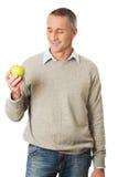 Lycklig mogen man med ett äpple Royaltyfria Foton