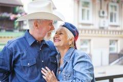Lycklig mogen man och kvinna som mot varandra lutas Mogen man och kvinna som ler att luta mot varandra Royaltyfri Bild