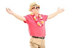 Lycklig mogen man på en semester som fördelar hans armar Arkivbild