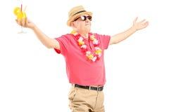 Lycklig mogen man på en semester som rymmer en coctail och en fördelning Arkivfoton