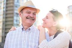 Lycklig mogen man som ler med den unga kvinnan arkivfoto