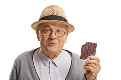 Lycklig mogen man som rymmer en biten chokladstång arkivbild