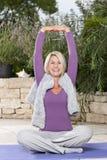 Lycklig mognad kvinna som gör yoga arkivfoto