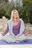 Lycklig mognad kvinna som gör yoga royaltyfria bilder