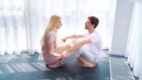 Lycklig morgon av unga älska par som sitter på golv och rymmer händer lager videofilmer