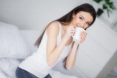 lycklig morgon St?ende av en le n?tt ung brunettkvinna som kopplar av i vit s?ng arkivbilder