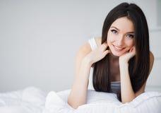 lycklig morgon St?ende av en le n?tt ung brunettkvinna som kopplar av i vit s?ng arkivbild