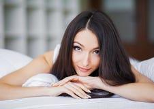 lycklig morgon St?ende av en le n?tt ung brunettkvinna som kopplar av i vit s?ng royaltyfri foto