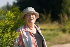 Lycklig mormor - hög kvinna i den vita hatten som ler i parkera eller trädgården royaltyfria bilder
