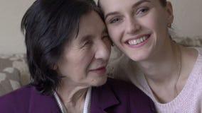 Lycklig mormor och dotter som ler, embarcing som visar förälskelse, affektion långsamt lager videofilmer