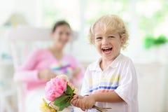 Lycklig mother'sdag Barn med g?va f?r mamma arkivbild