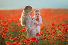 lycklig motherhood Mamma- och sondottern spelar i fältet av att blomma röda vallmo arkivbilder