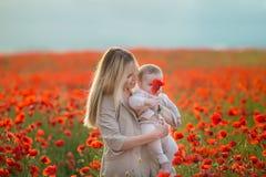 lycklig motherhood Mamma- och sondottern spelar i fältet av att blomma röda vallmo arkivfoto