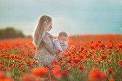 lycklig motherhood Mamma- och sondottern spelar i fältet av att blomma röda vallmo arkivfoton