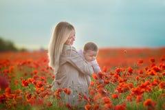 lycklig motherhood Mamma- och sondottern spelar i fältet av att blomma röda vallmo royaltyfri fotografi