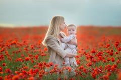 lycklig motherhood Mamma- och sondottern spelar i fältet av att blomma röda vallmo royaltyfri foto