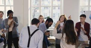 Lycklig multietnisk grupp för affärsfolk som dansar fira tillsammans ferier Roligt parti på den moderna sunda arbetsplatsen arkivfilmer