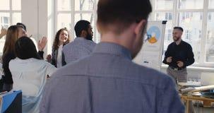 Lycklig multietnisk grupp för affärsfolk som gör rolig framgångberömdans på det moderna moderiktiga kontorsarbetsplatspartiet stock video
