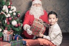 Lycklig multiraceal pojke och Santa Claus med den stora gåvaasken Arkivbilder