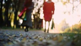 Lycklig mum och dotter med färgrika shoppingpåsar som går till och med parkera i hösten på suddig bokehbakgrund stock video