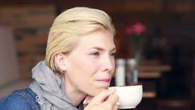 Lycklig nätt blondin som dricker kaffe stock video