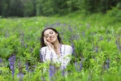 Lycklig nätt brunettkvinna i blommafält Arkivfoto