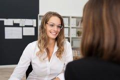 Lycklig nätt kontorskvinna som talar till Kontor-kompisen Royaltyfri Fotografi