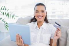 Lycklig nätt kvinna som köper direktanslutet genom att använda hennes minnestavlaPC Fotografering för Bildbyråer