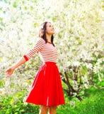 Lycklig nätt kvinna som tycker om luktblommor över vårträdgård royaltyfria foton