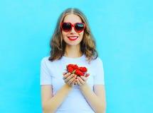 Lycklig nätt le kvinna med många jordgubbe över blått Royaltyfri Fotografi