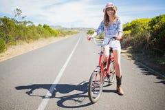 Lycklig nätt modell som poserar, medan rida cykeln Arkivbilder