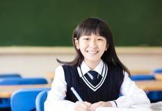 Lycklig nätt studentflicka med böcker i klassrum Royaltyfri Bild