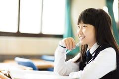 Lycklig nätt studentflicka med böcker i klassrum Royaltyfria Foton
