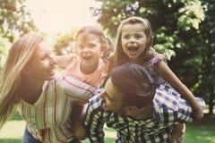 lycklig natur för familj Föräldrar som bär deras dotter på piggy royaltyfria foton