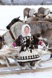 Lycklig Nenets flicka i medborgarekläder bland den nordliga domestien Royaltyfria Bilder