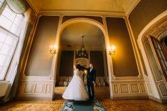 Lycklig nygift personpardans i ljus korridor med den lyxiga tappninginre royaltyfri fotografi