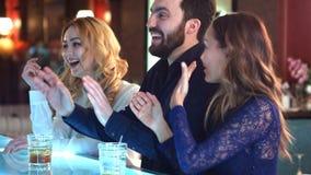 Lycklig och attraktiv grupp av vänner som tillsammans pratar och skrattar i en stång Arkivfoton