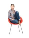 Lycklig och bekymmerslös tonårs- flicka i stol Arkivfoto