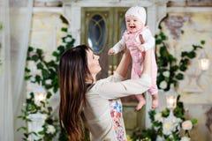 Lycklig och härlig mammabrunett som rymmer en charmig liten daugh royaltyfri fotografi