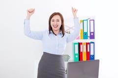 Lycklig och lyckad affärskvinna som lyfter hennes armar på kontorsbakgrund och firar framgång som isoleras på vit Åtlöje upp royaltyfri fotografi
