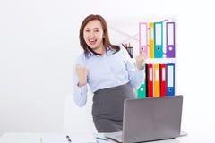 Lycklig och lyckad affärskvinna som lyfter hennes armar på kontorsbakgrund och firar framgång som isoleras på vit Åtlöje upp royaltyfria foton