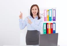 Lycklig och lyckad affärskvinna som lyfter hennes armar på kontorsbakgrund och visar något som isoleras på vit Åtlöje upp royaltyfri bild