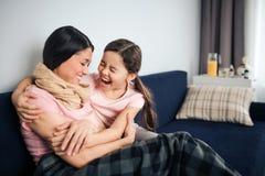 Lycklig och positiv ung kvinna att sitta samman med hennes dotter på soffan i rum De skrattar ut högt Den unga kvinnan är sjuk fotografering för bildbyråer