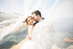 Lycklig och romantisk plats av precis gifta unga brölloppar som poserar på den härliga stranden arkivbilder