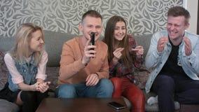 Lycklig och tillfällig grupp av unga vänner och att hänga ut hemma tillsammans och att lyssna till musik via en television royaltyfri bild