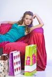 Lycklig och trött kvinna som vilar, når att ha shoppat arkivfoto