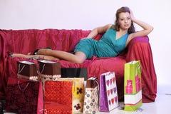 Lycklig och trött kvinna som vilar, når att ha shoppat royaltyfria bilder
