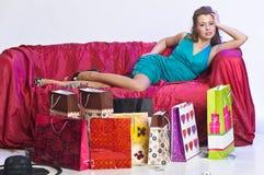 Lycklig och trött kvinna som vilar, når att ha shoppat arkivfoton